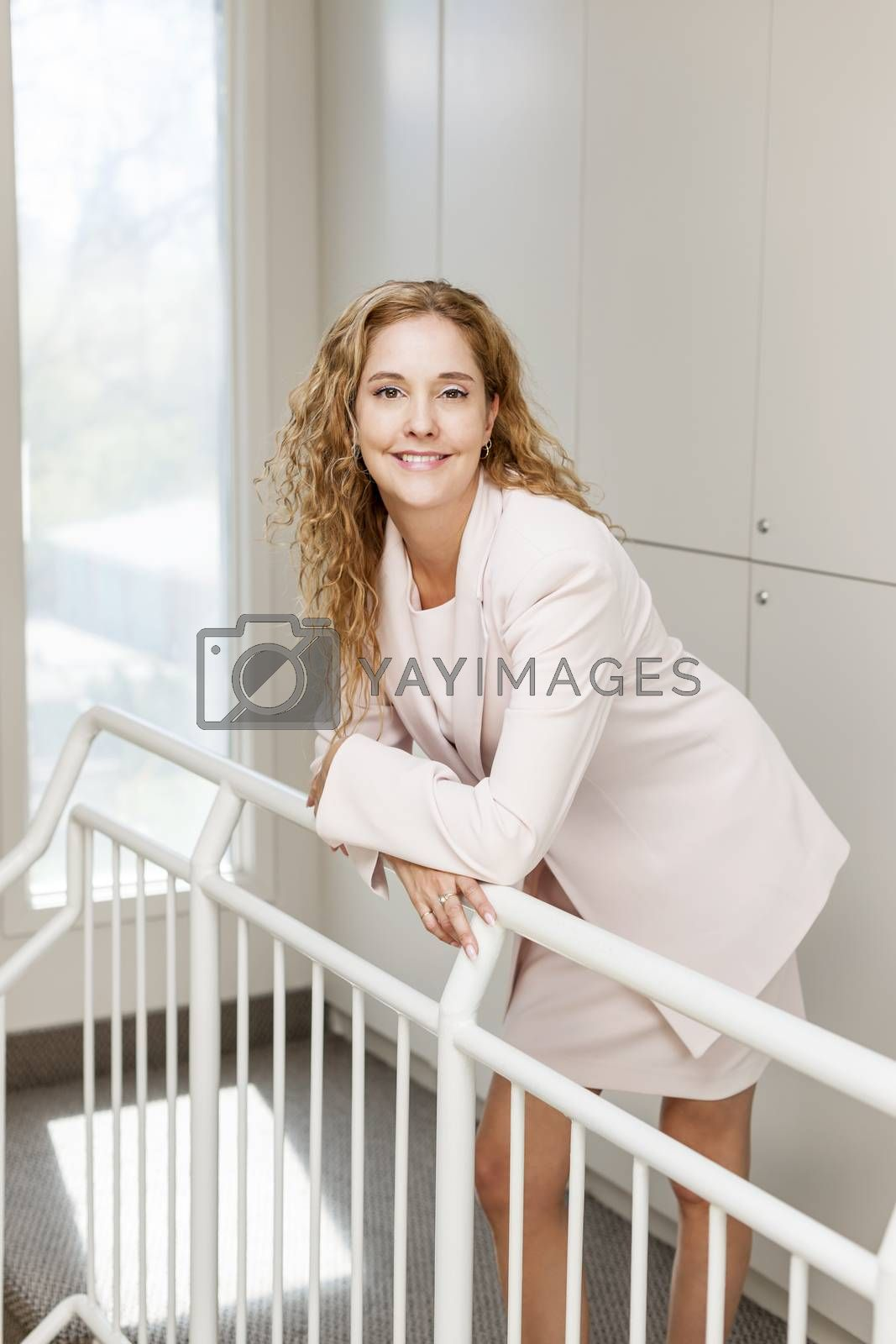 Smiling proud business woman standing in office hallway leaning on railing