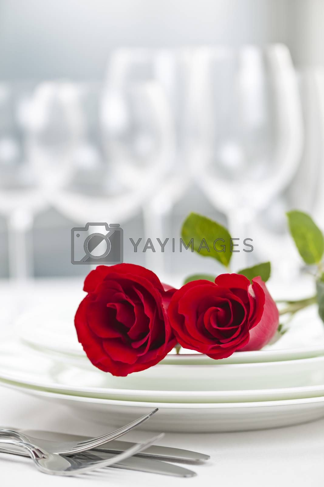 Romantic restaurant table setting for two with roses plates and cutlery
