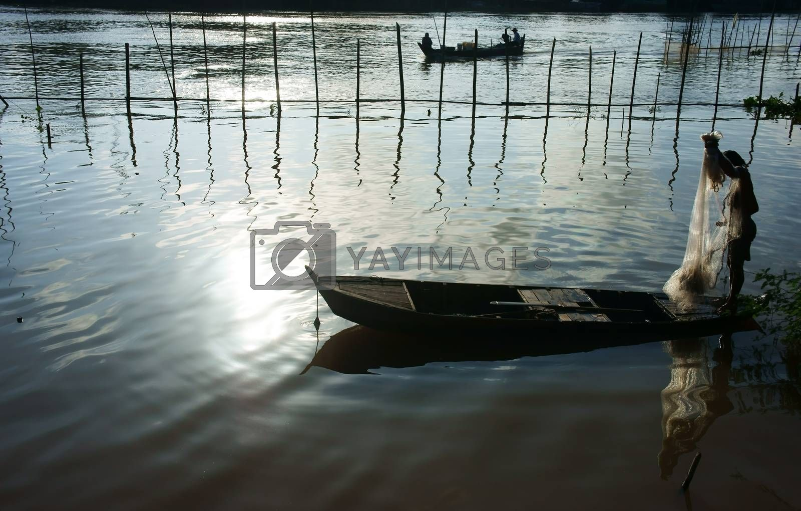 silhouette  's fisherman standing on row boat, pick up the net, repair for fishing to catch fish on river at morning in flood season