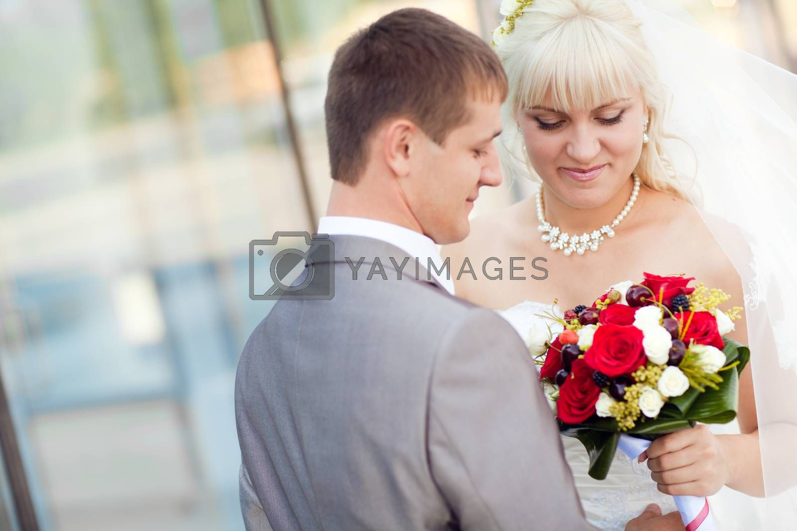 bride and groom by the glass wall