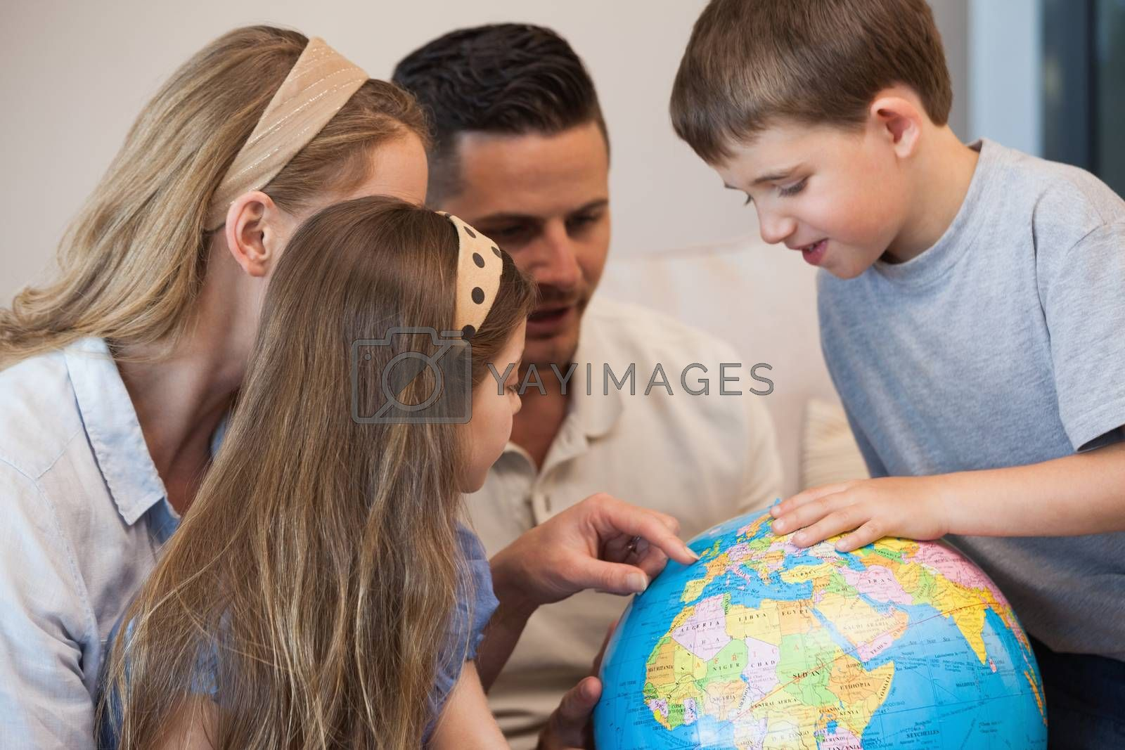 Close-up of a family of four looking at globe in the house