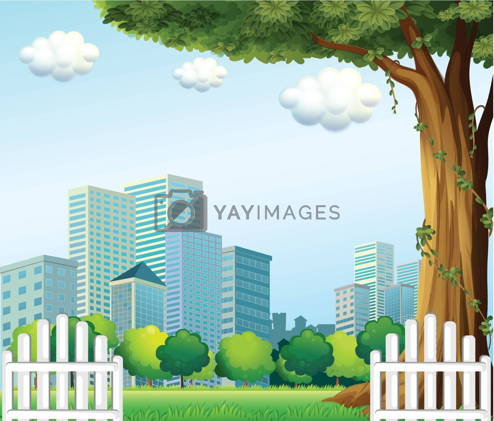 Royalty free image of A giant tree near the wooden fence across the tall buildings by iimages