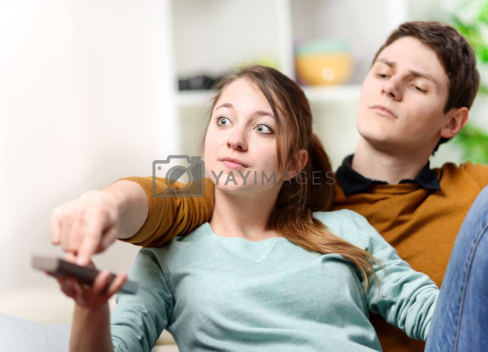beautiful woman and her husband trying to change tv channel on remote control