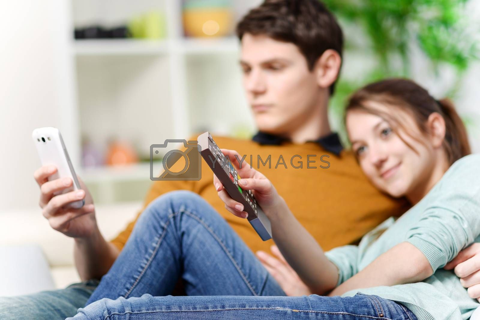 beautiful woman watching tv while her lover is watching a screen of cell