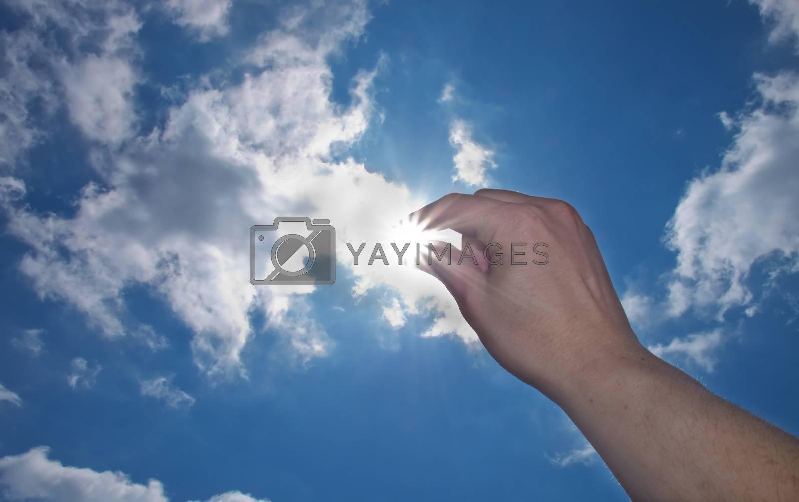 hand catch the sun on blue sky background