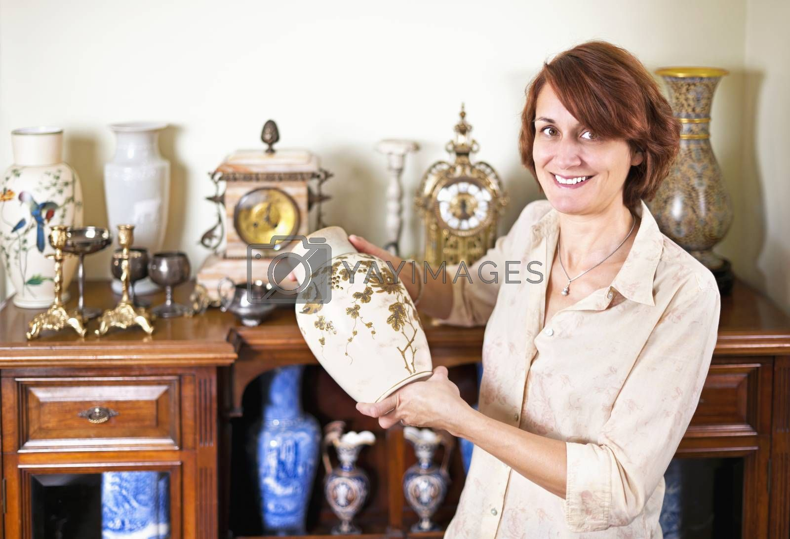 Proud woman holding vase from her collection of antiques