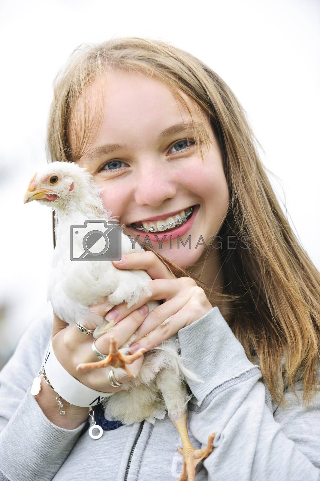 Smiling teenage girl with braces holding young chicken