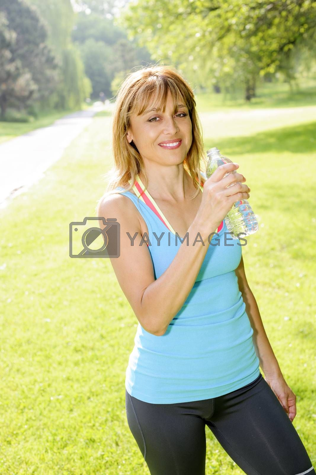 Smiling female fitness instructor taking a break with water bottle while exercising outdoor