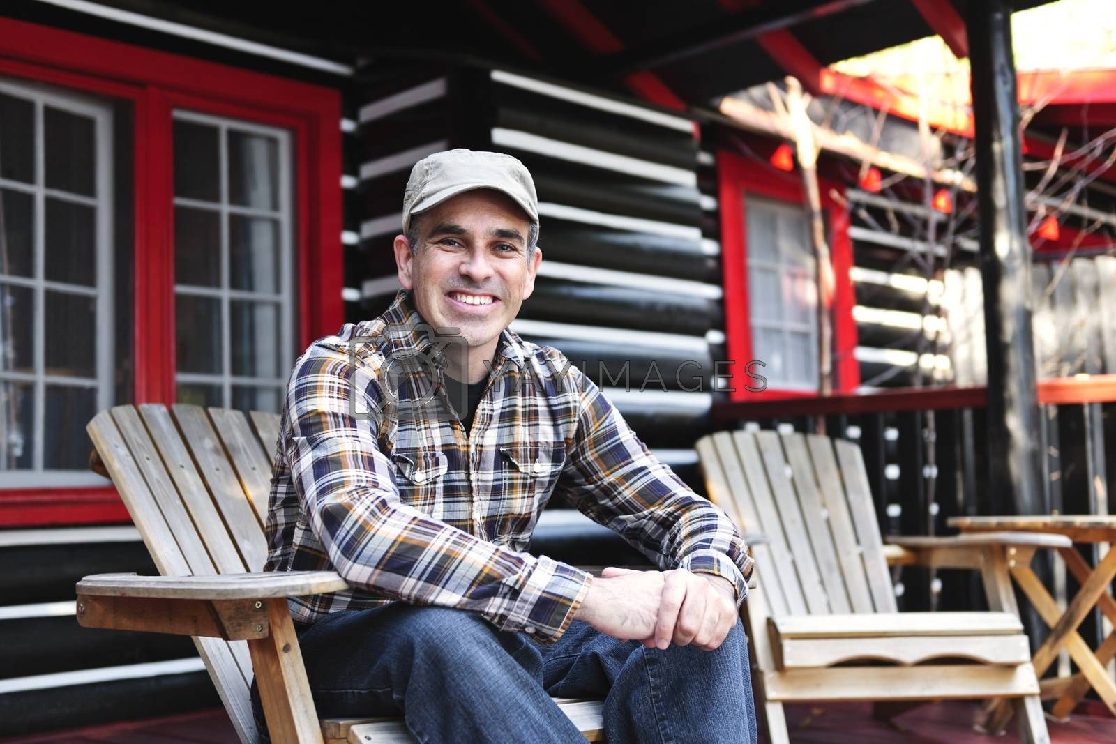 Smiling man sitting on cottage deck in wooden adirondack chair