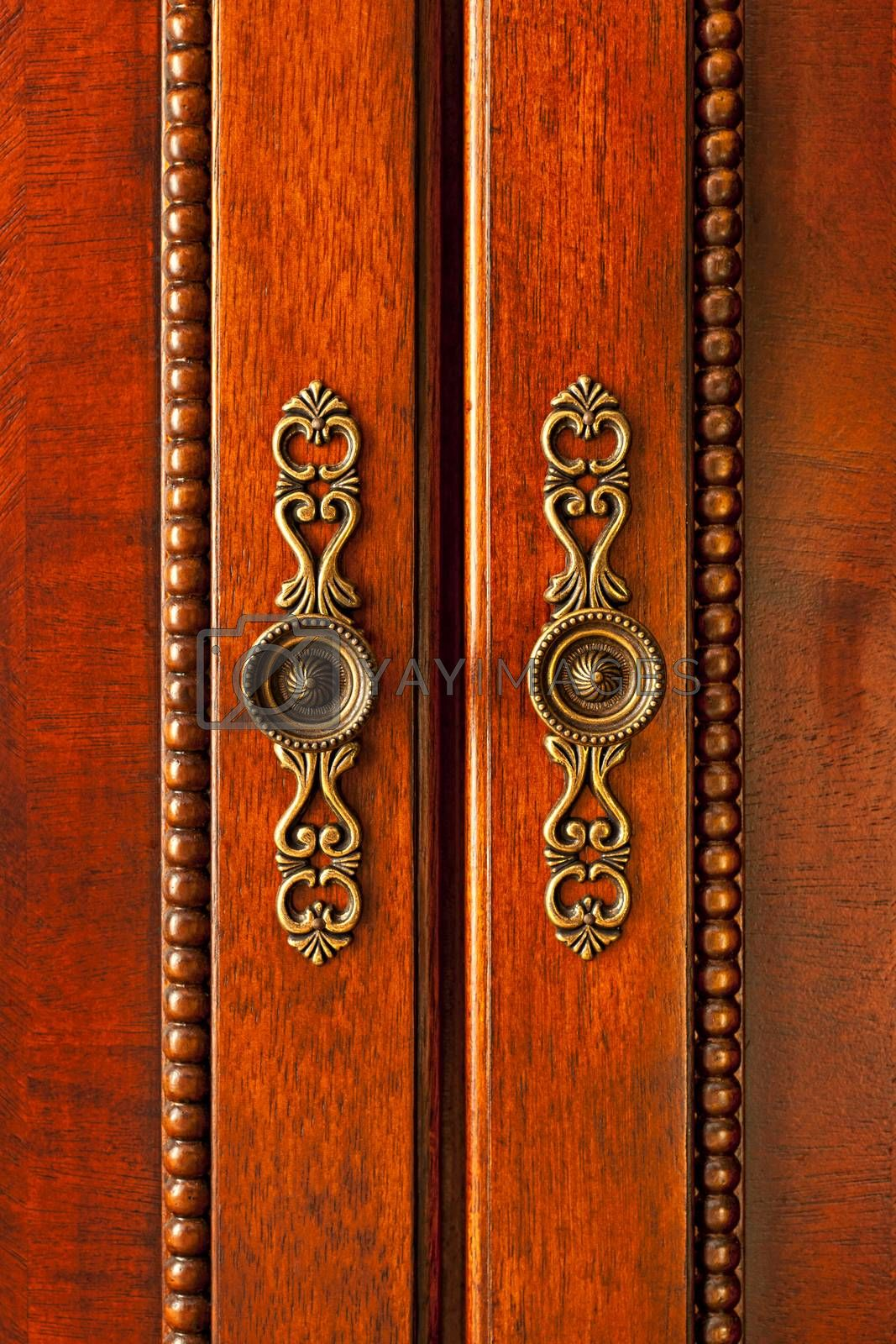 Ornate handles on wooden cabinet doors closeup