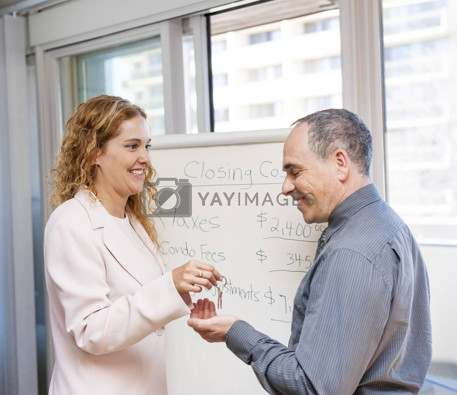 Female real estate agent giving keys to new home buyer