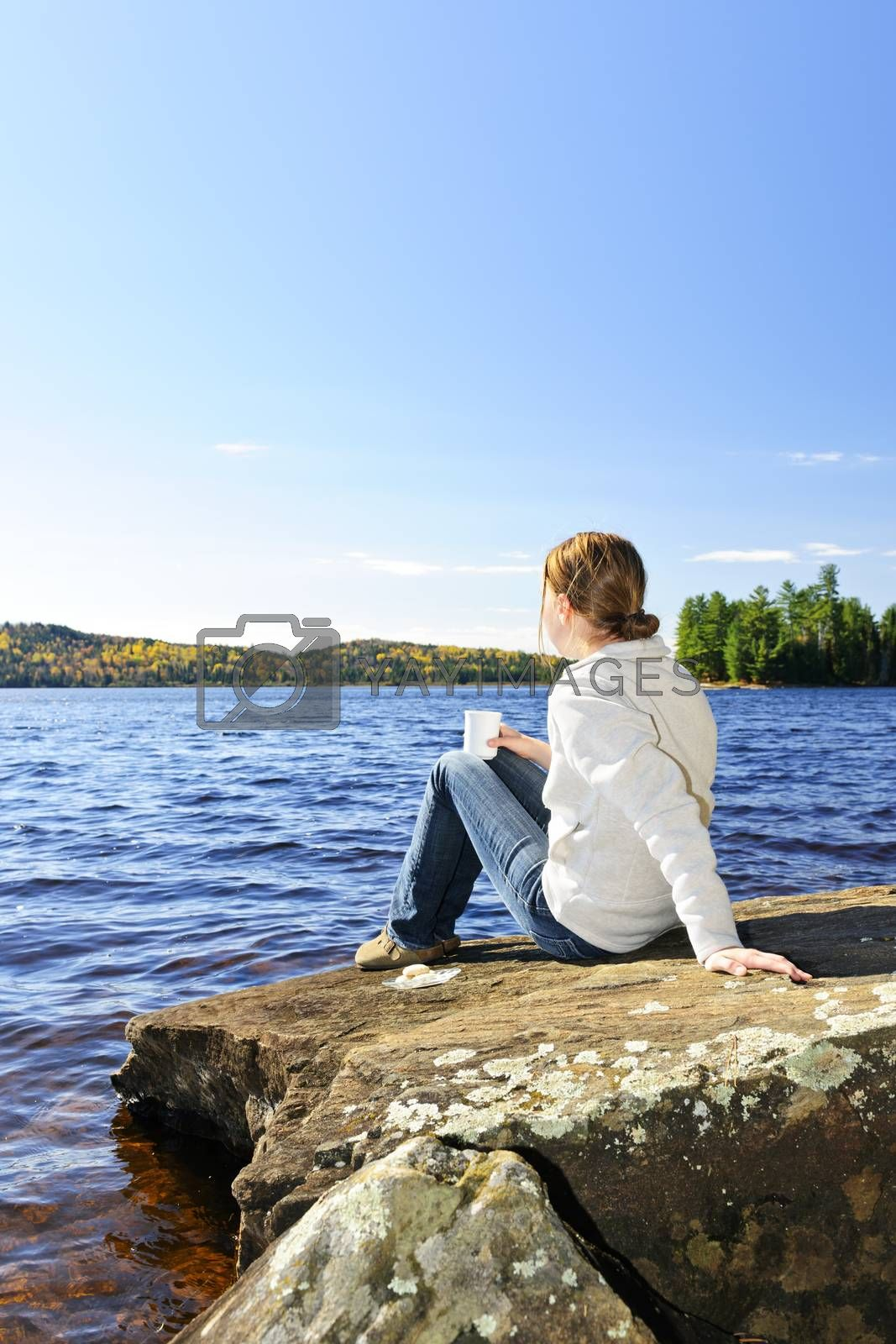 Woman relaxing by beautiful lake on sunny fall day in Algonquin Park, Canada