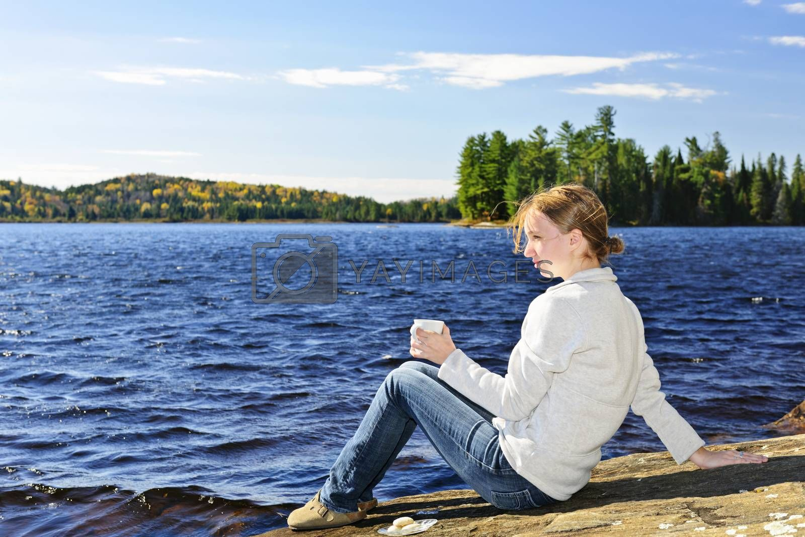 Young woman sitting with beverage on rock relaxing by beautiful lake in Algonquin Park, Canada.