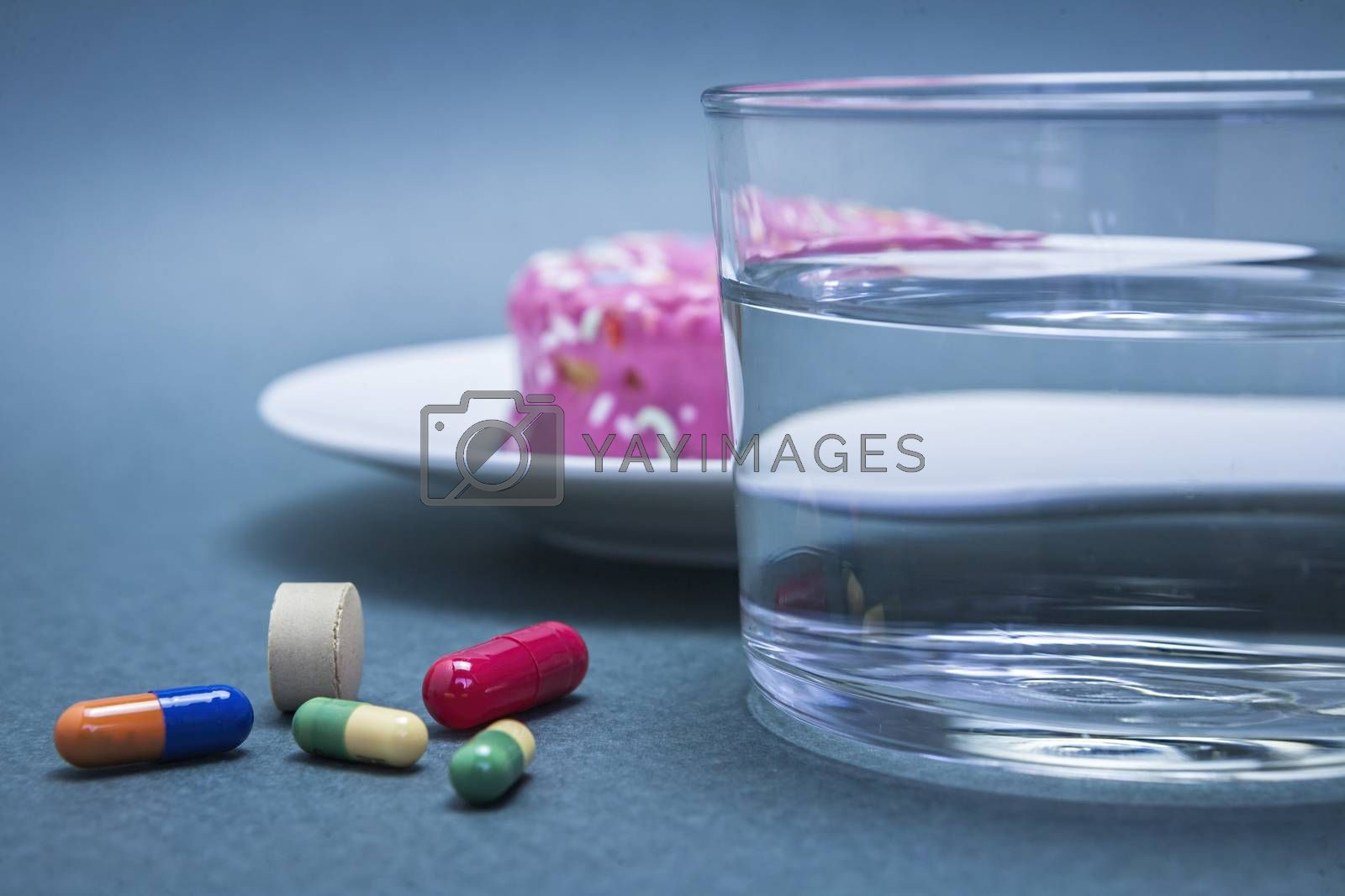 Various medicines to combat diabetes along with a sweet cake and glass water, concept of disease of hyperglycemia or diabetes