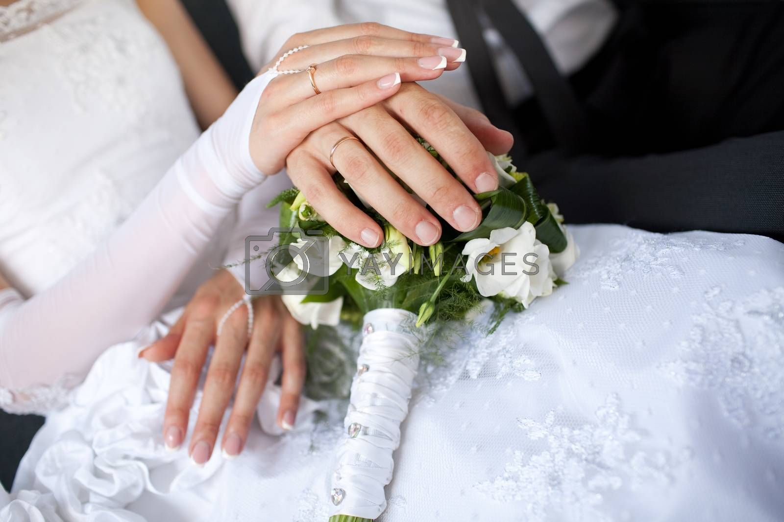 hands with wedding rings over the bouquet