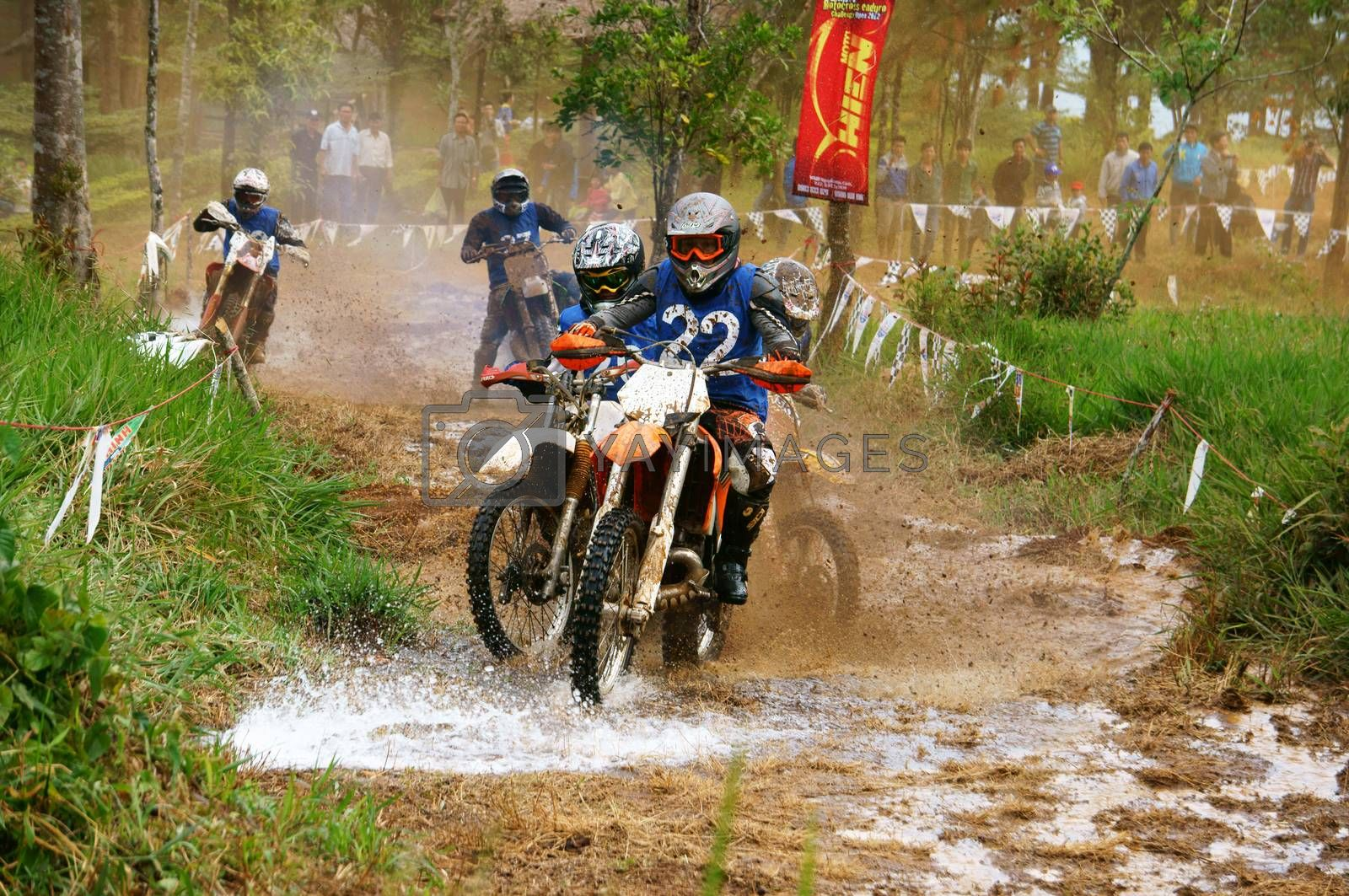 BAO LOC, VIET NAM- DECEMBER 23:  Racer in activity at motorcycle race hole on Bao Loc, Viet Nam, they try to across a marshy stretch of road with violent competition in December 23, 2012