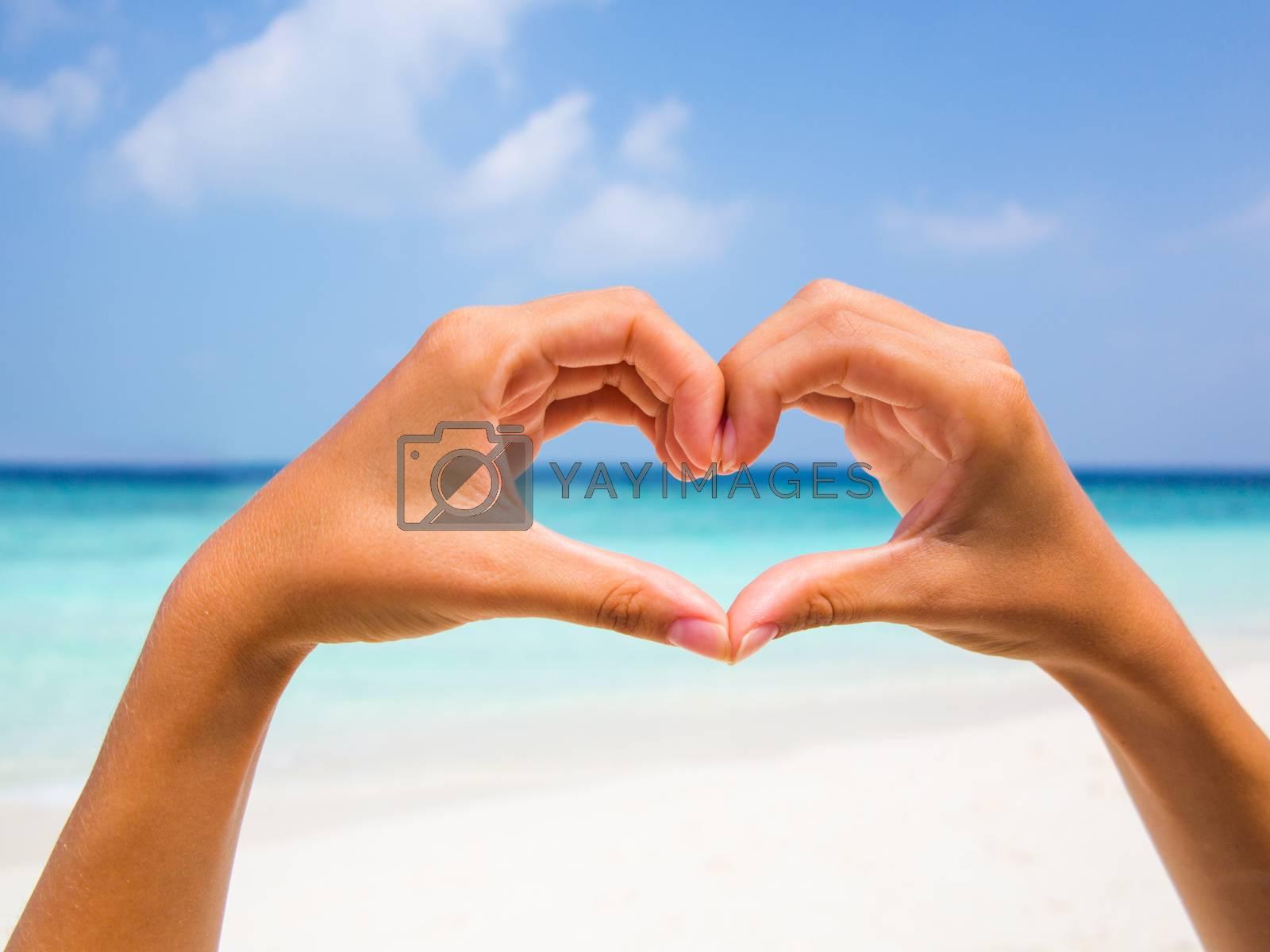 Hands making a heart shape on the beach backgound