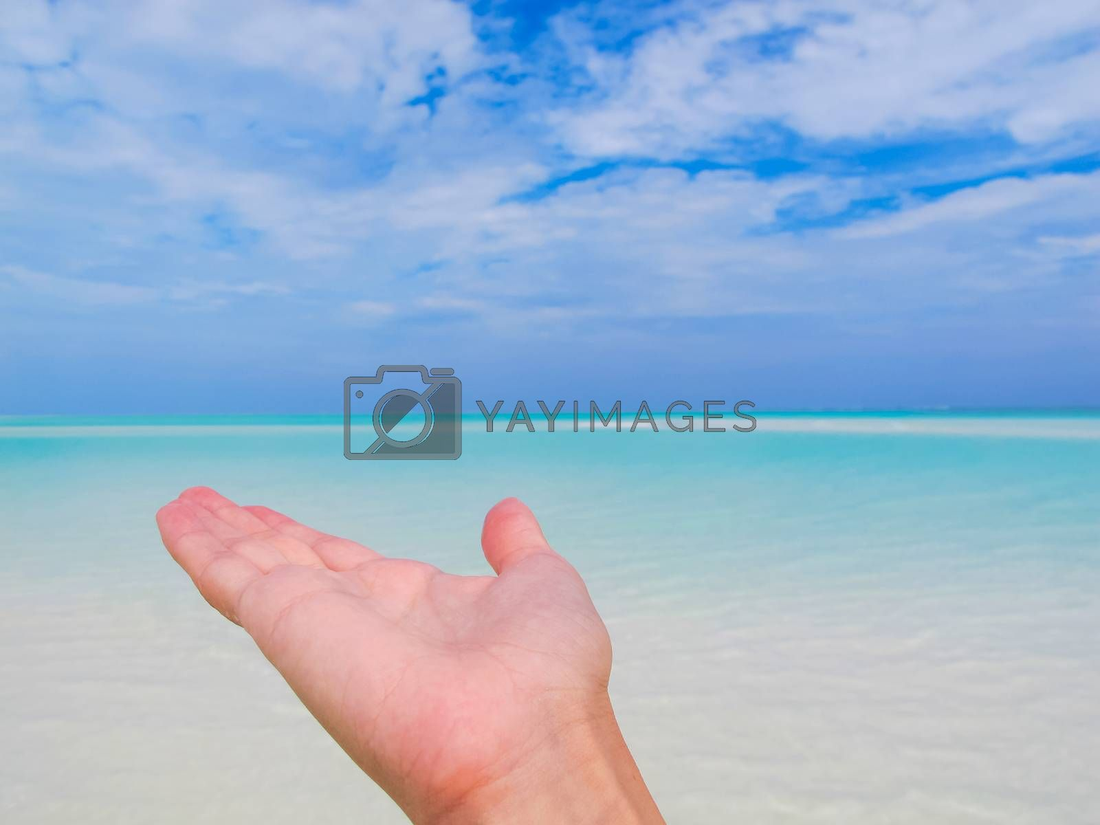 Showing hand, beach at the background