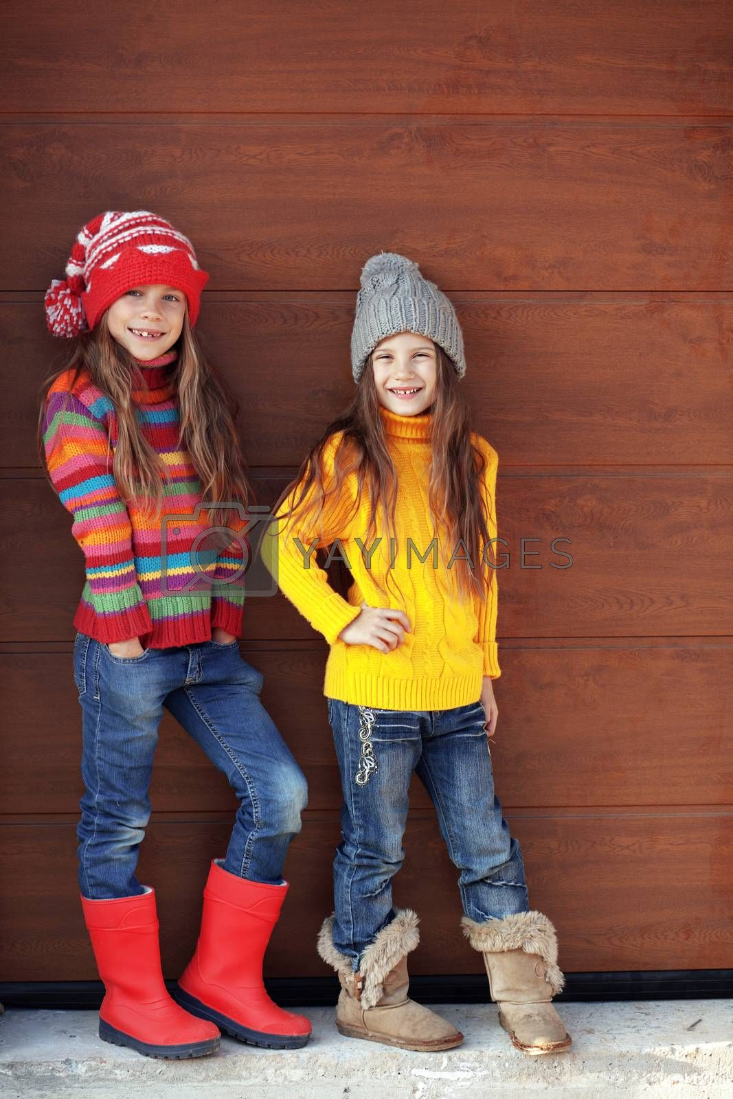 Cute little girls wearing knit winter clothes posing over wooden background