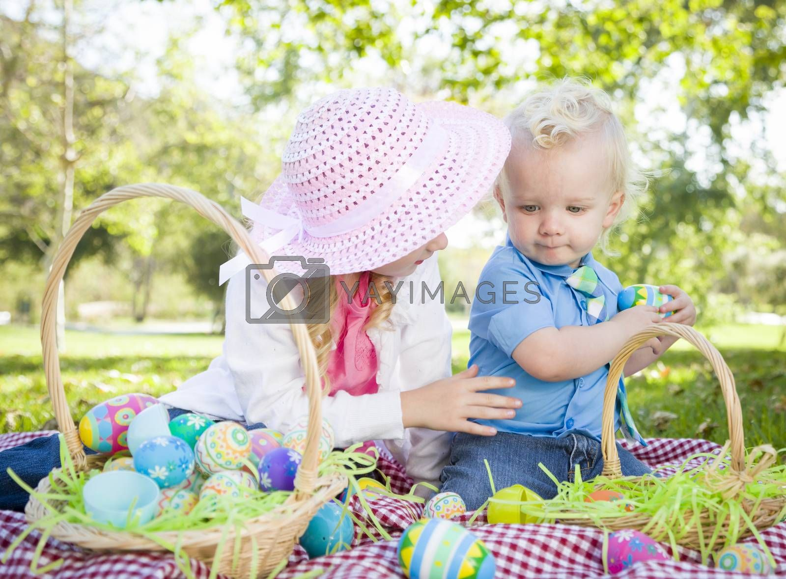 Cute Young Brother and Sister Enjoying Their Easter Eggs Outside in the Park Together.