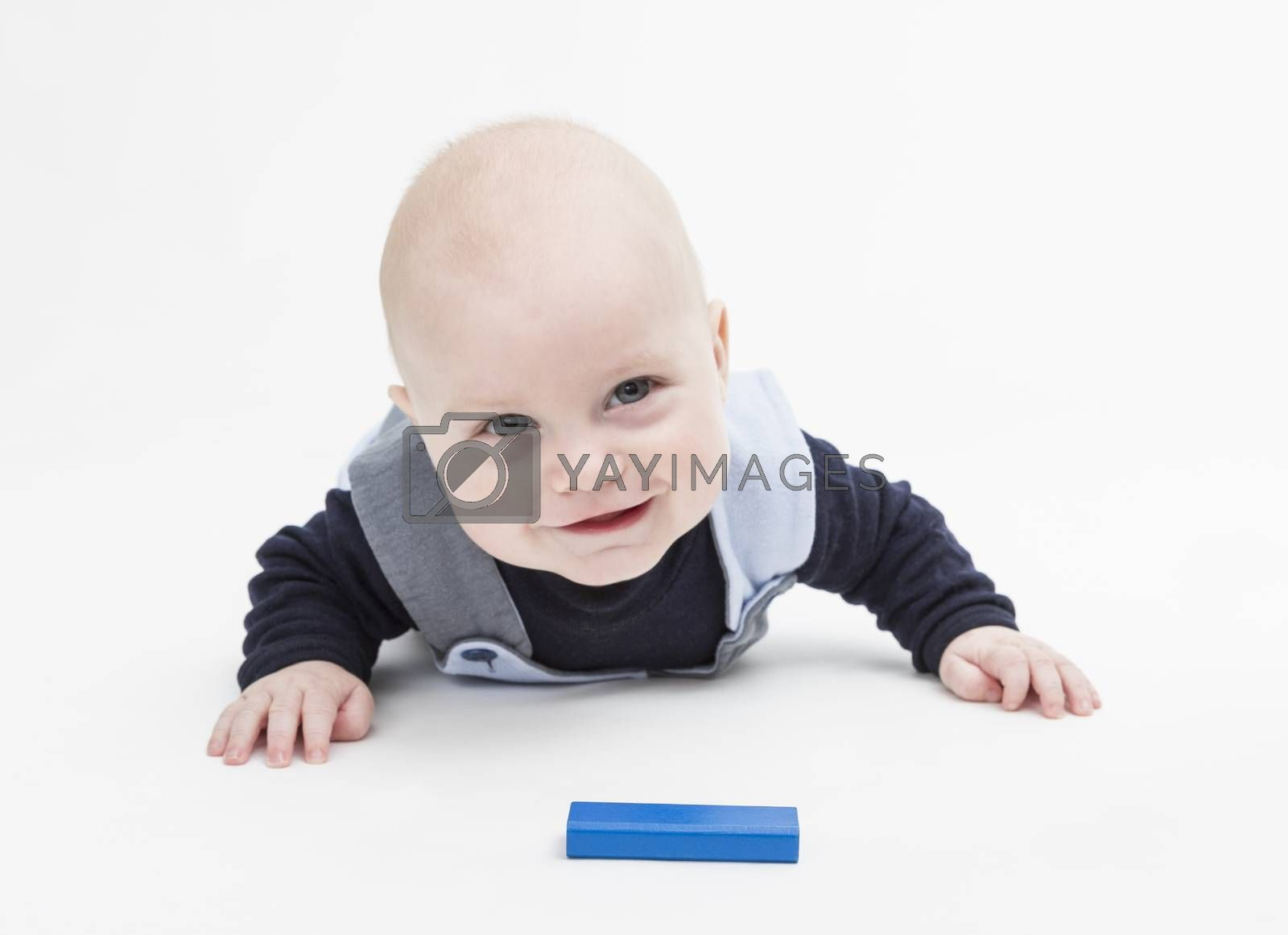 interested baby with toy block on floor isolated on white