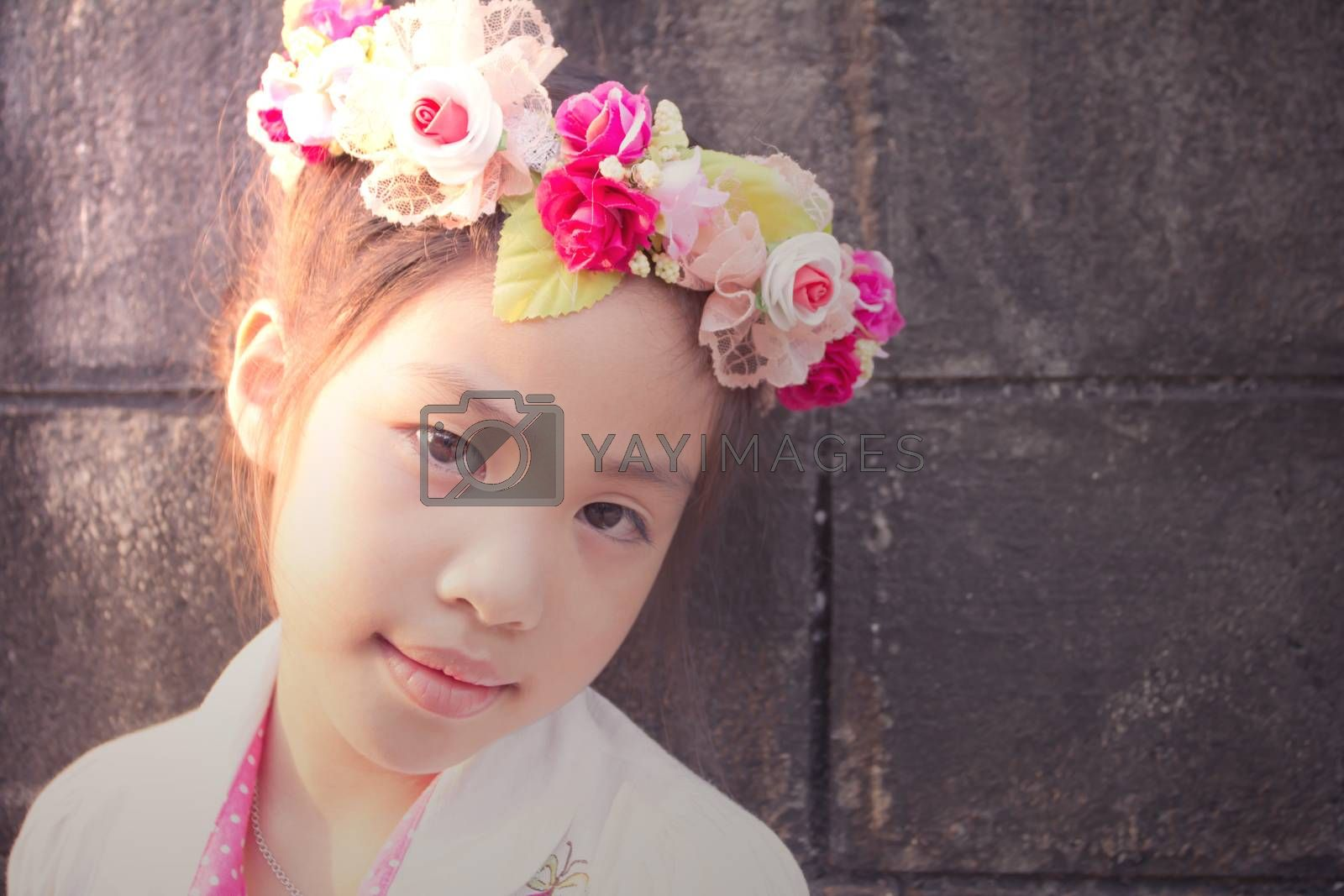 Lovely little girl with flowers on the head, vintage texture