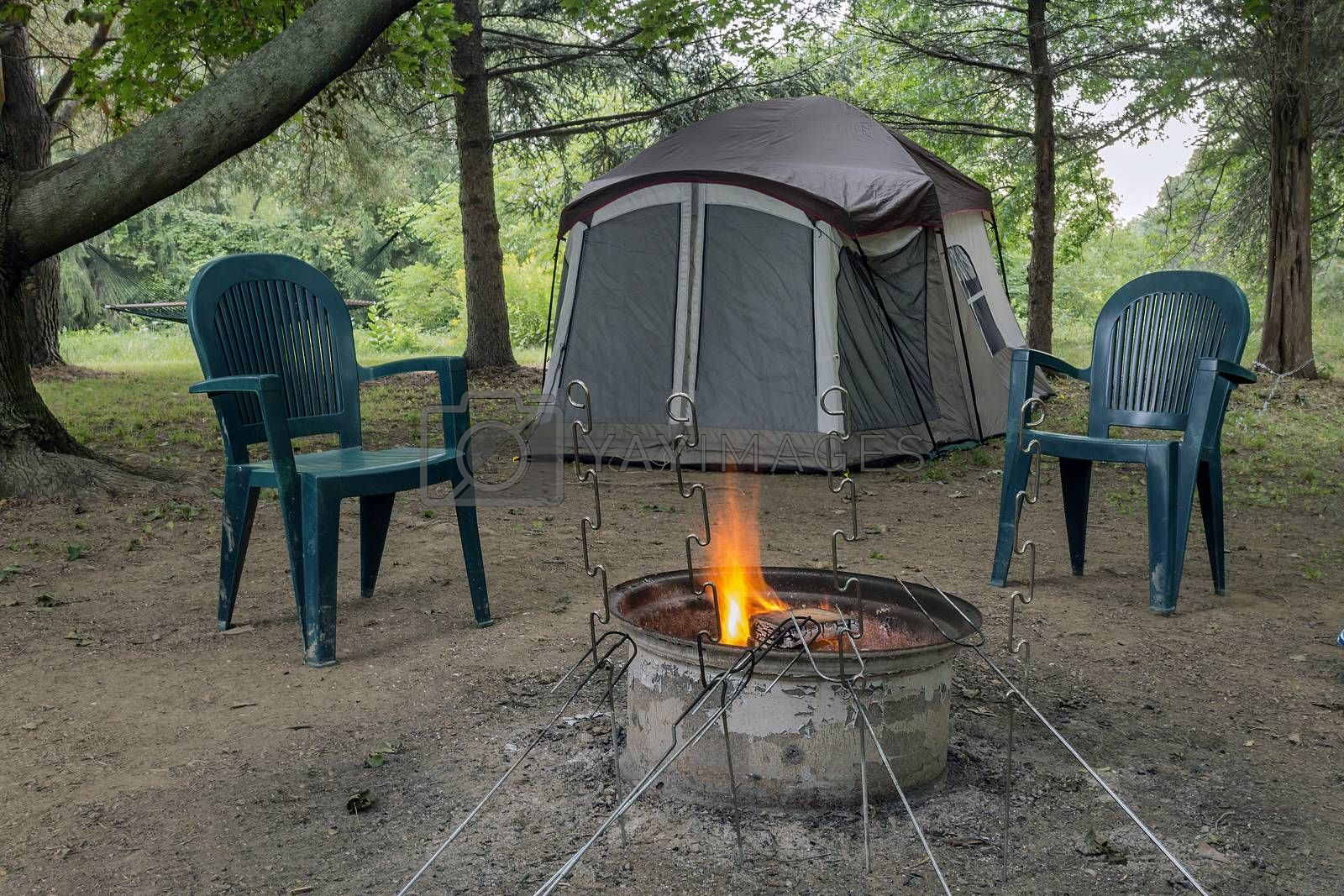 Pitched tent, crackling campfire, two chairs, and metal roasting sticks. All under a canopy of trees.