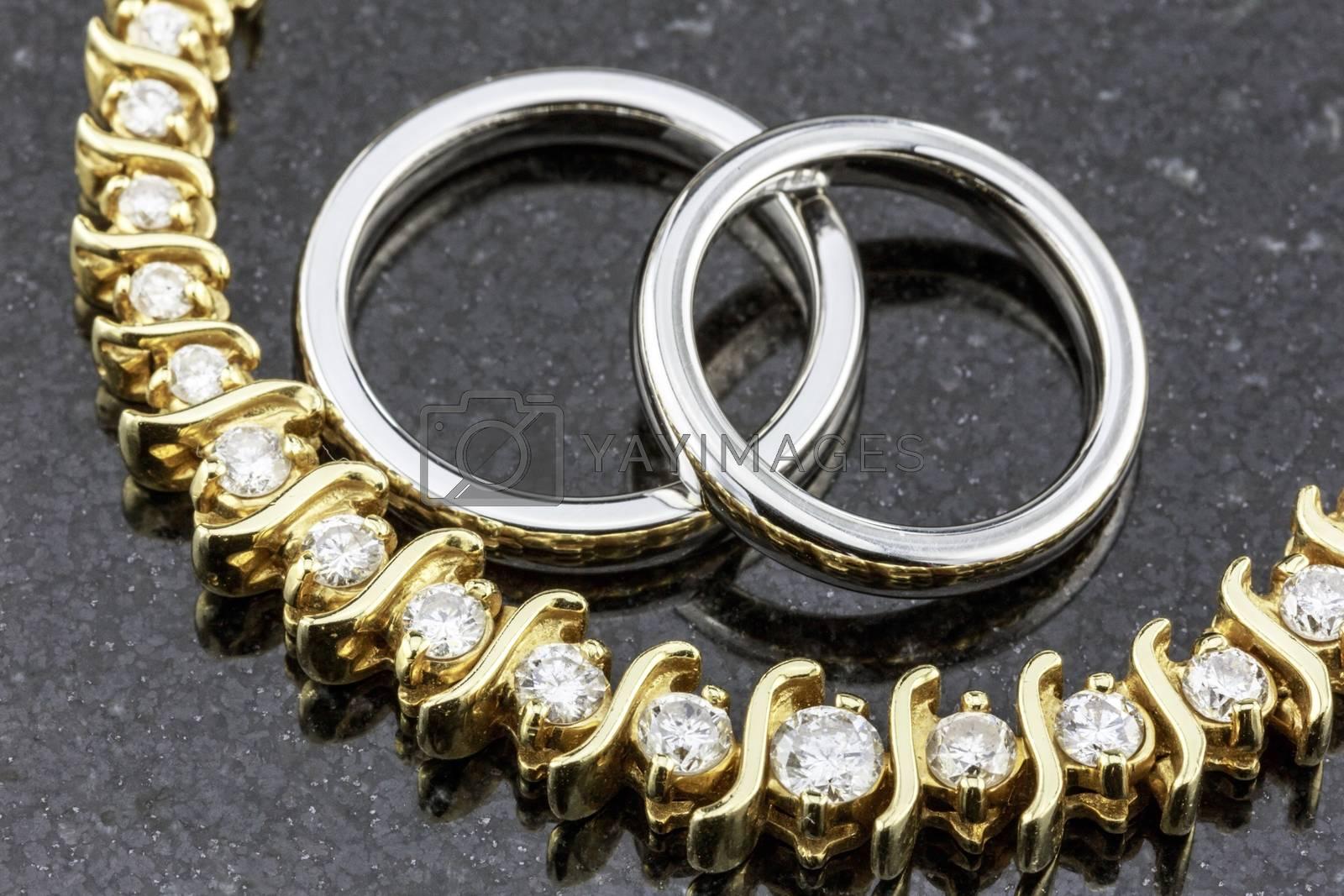 Titanium wedding bands and diamond necklace on black marble.