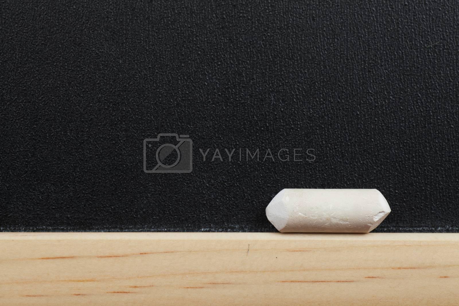 Closeup view of little chalk on the edge of blackboard