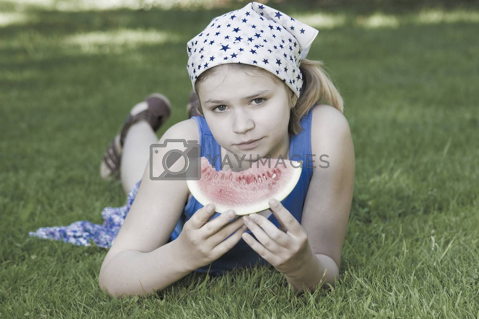 cute little girl eating watermelon on the grass by miradrozdowski
