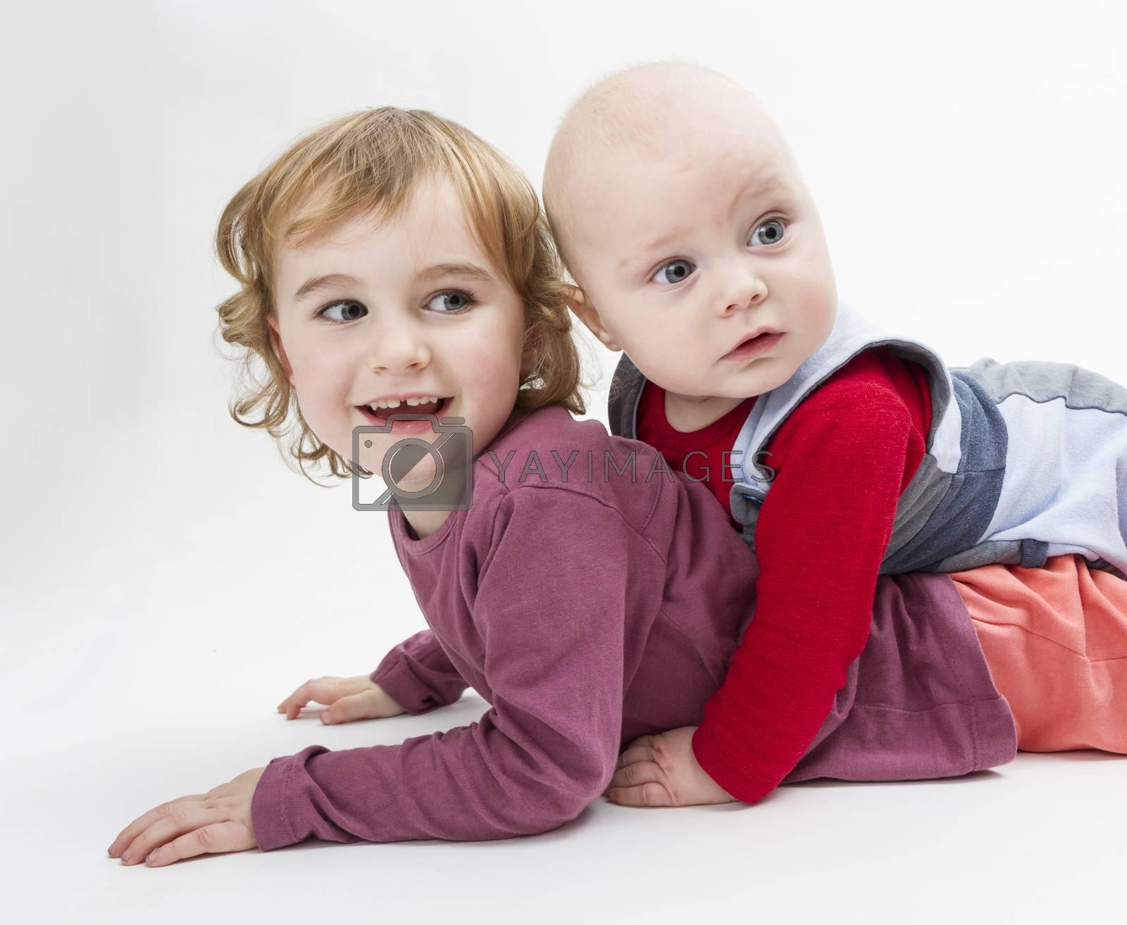 two siblings playing on floor. studio shot in grey background