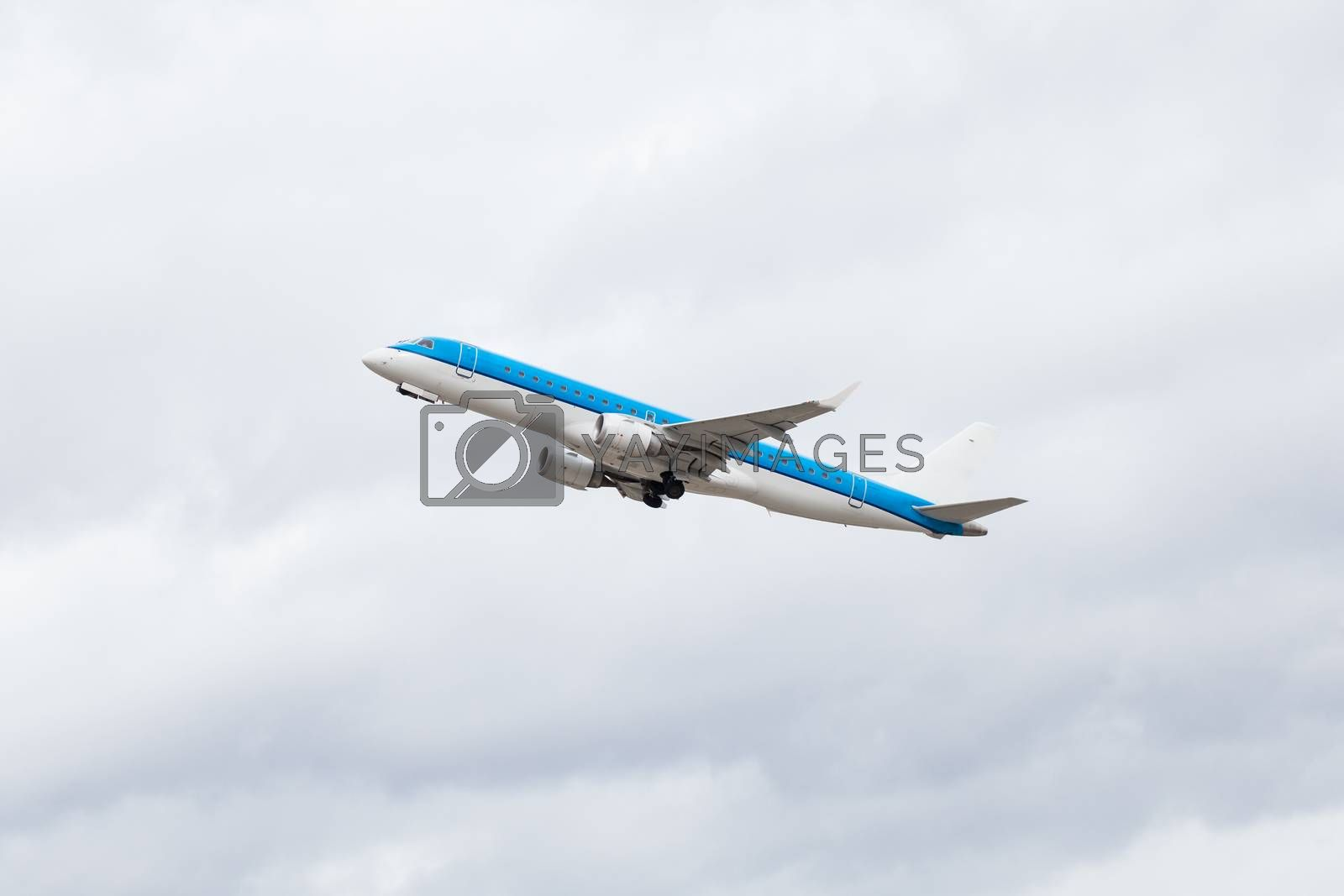 Commercial airliner flying midair after takeoff with the landing gear and wheels still extended as it climbs for height against a blue sky, conceptual of air travel