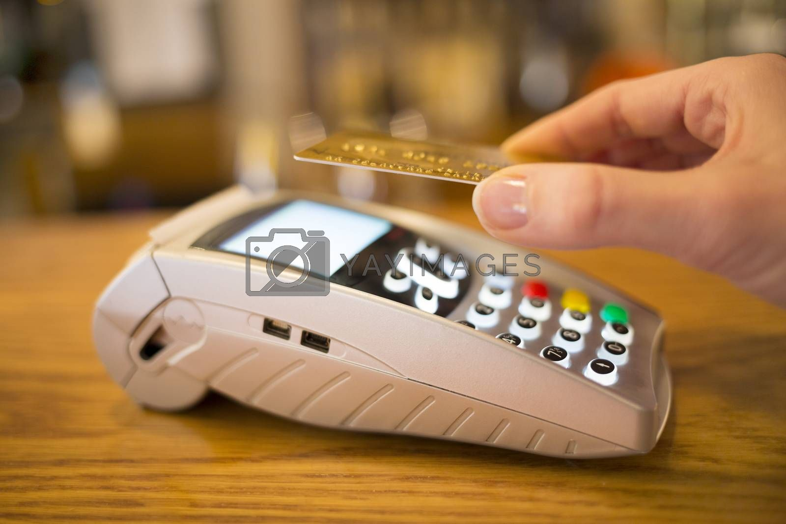 Woman paying with NFC technology on credit card, restaurant, sho by LDProd