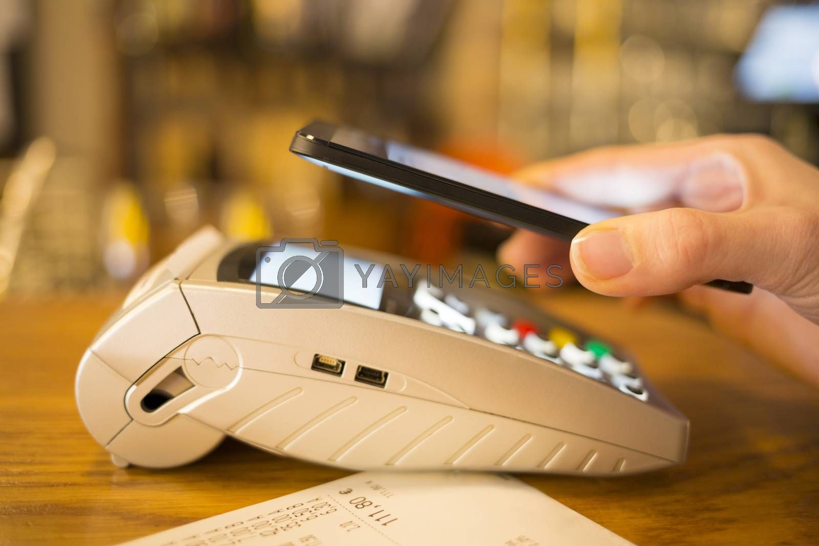 Woman paying with NFC technology on mobile phone, restaurant, sh by LDProd