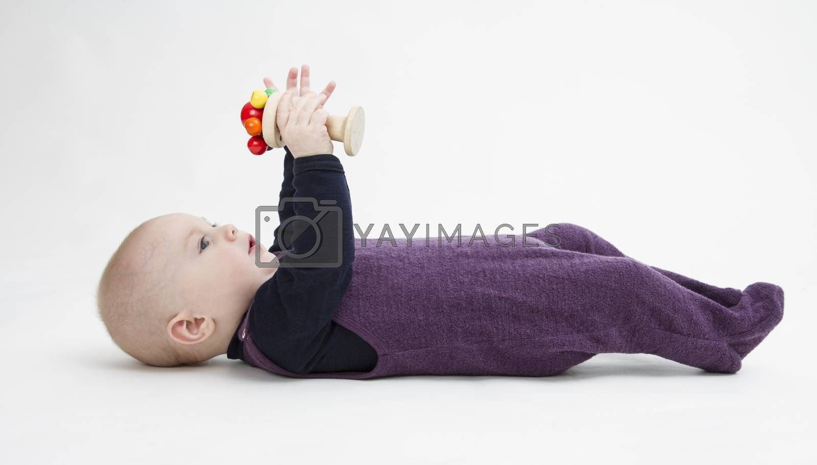 toddler lying on his back playing with wooden toy. grey background