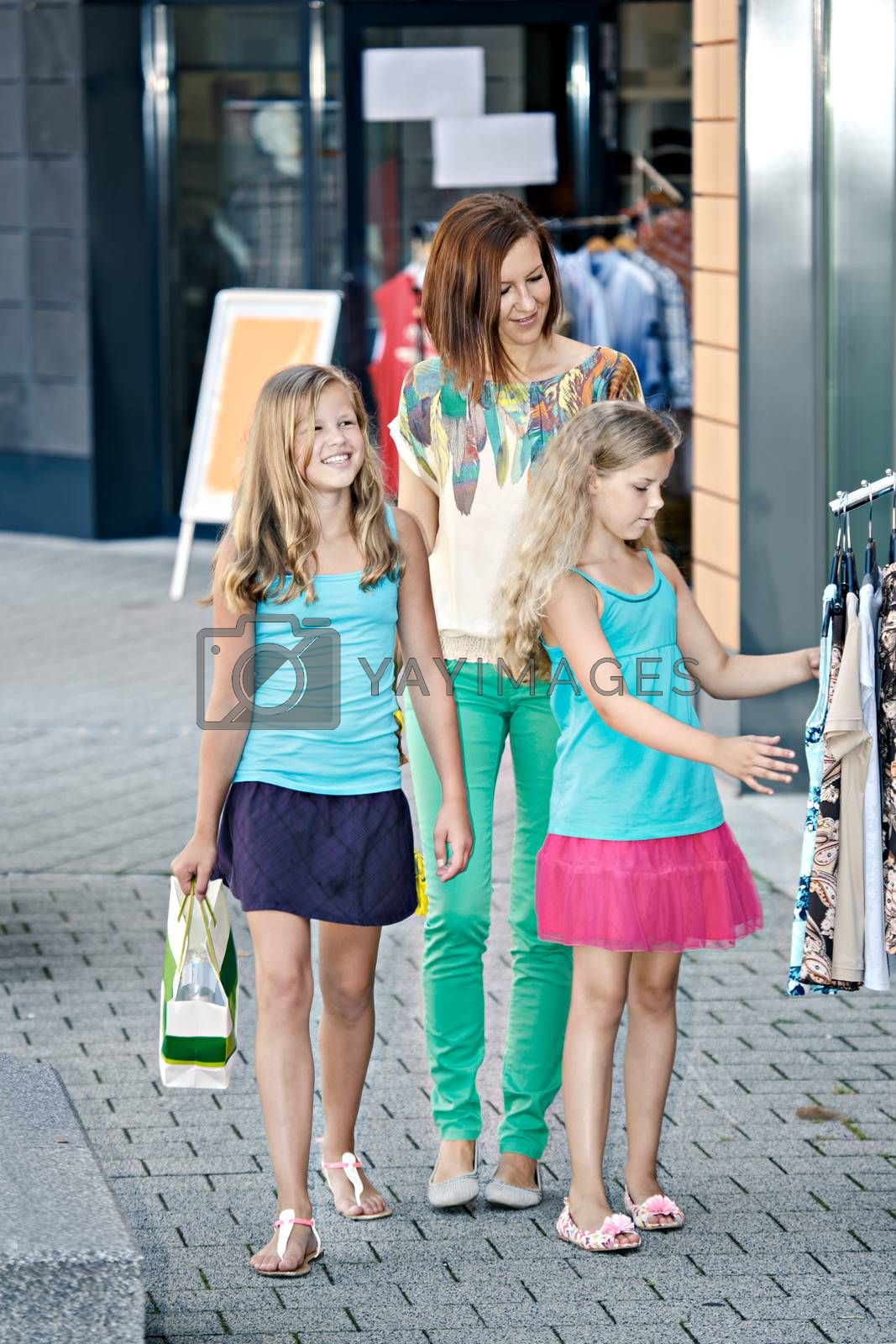 woman with two daughters shopping in an european city