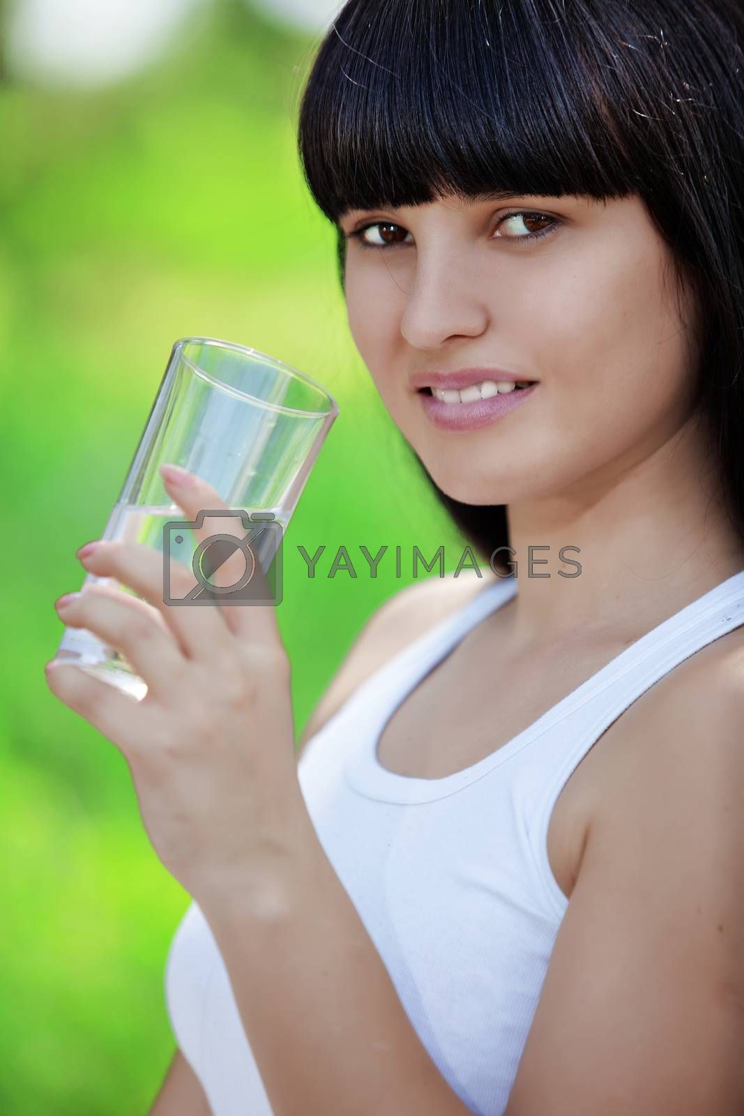 Portrait of young woman drinking water at green park