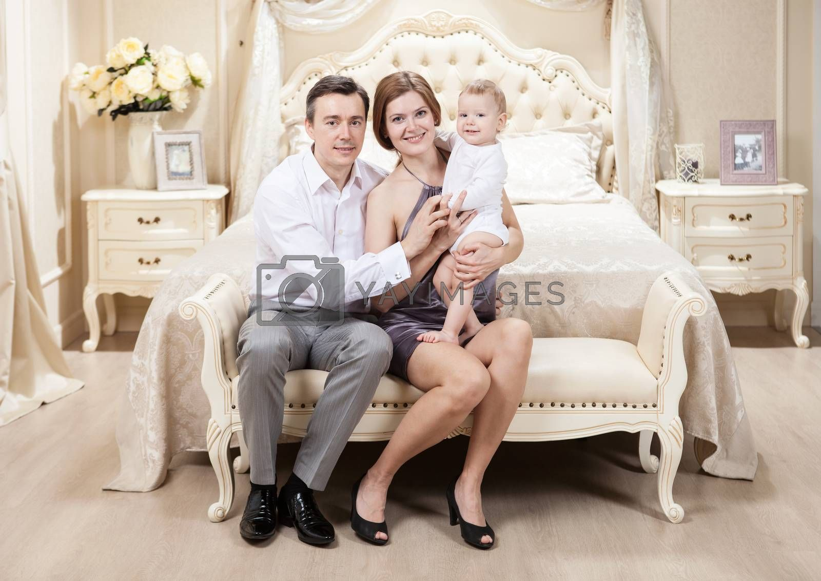 Young happy family with a baby on bed at home