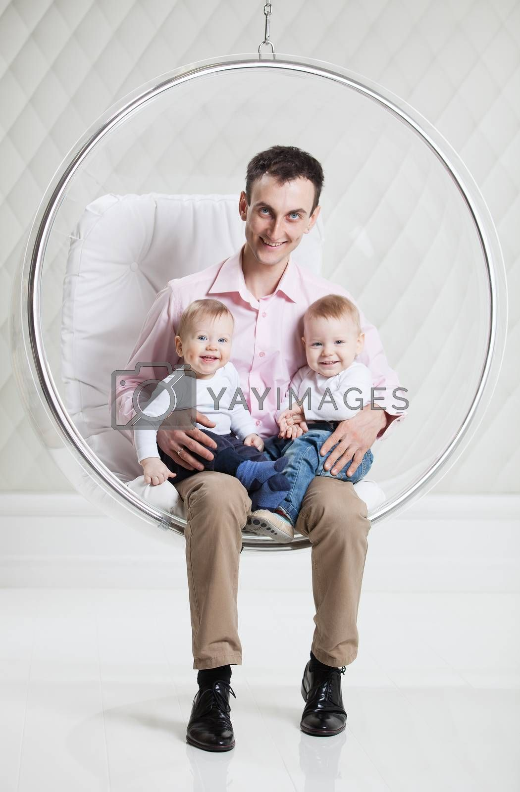 Young Caucasian man with two babies having fun while sitting in swinging hanging chair