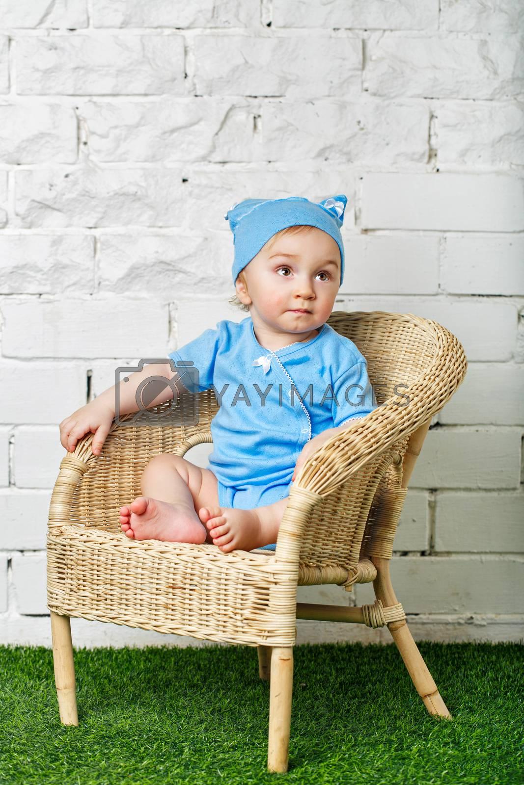 Little boy sitting in a wicker chair on the lawn barefoot