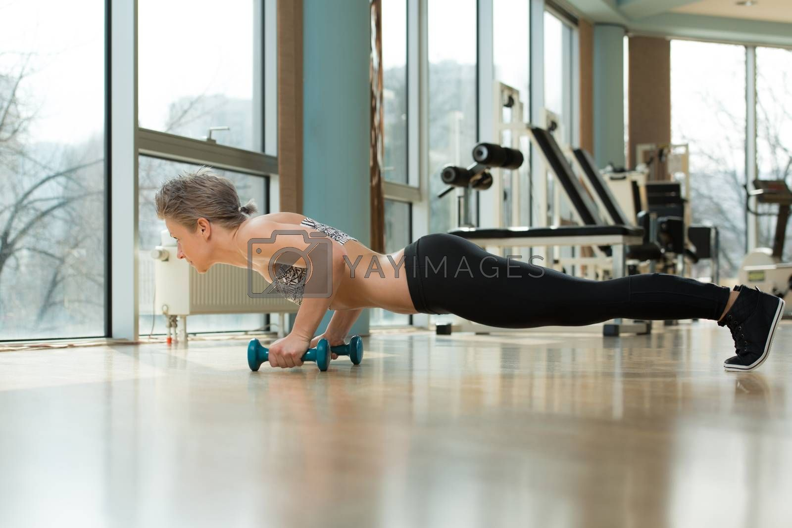 Royalty free image of Young Woman Doing Press Ups In Healthy Club by JalePhoto