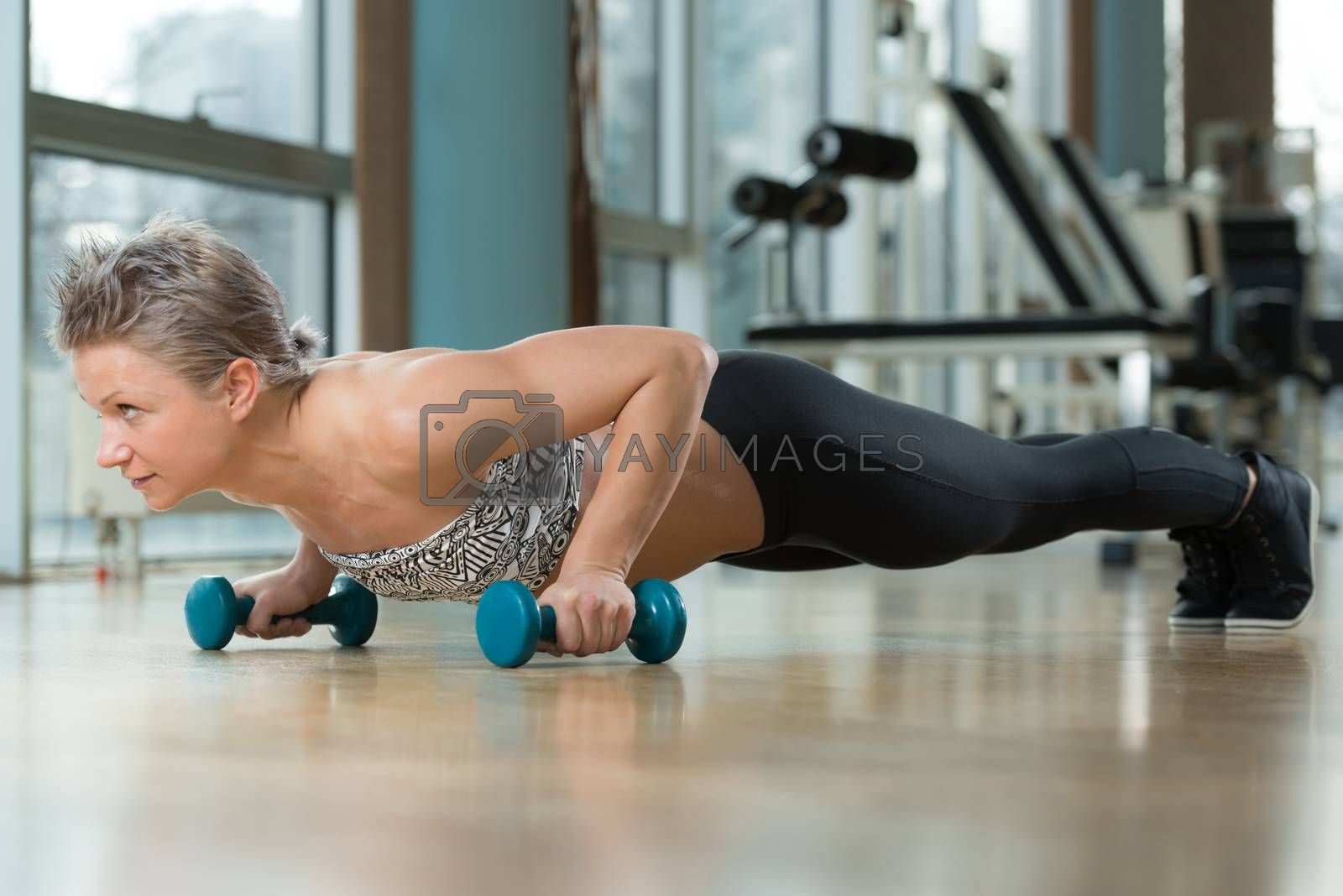 Royalty free image of Young Woman Exercising Push Ups by JalePhoto