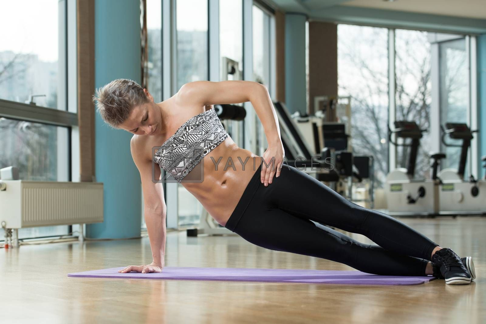 Attractive Female Athlete Performing Exercise For Abdominal Muscles