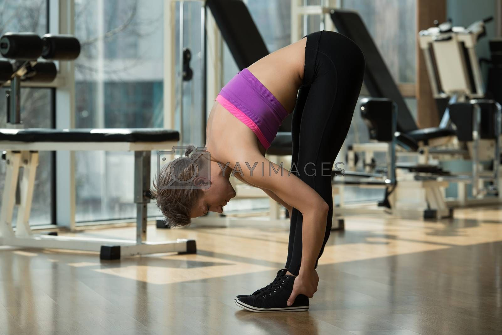 Fitness Woman Stretching  In A Healthy Club