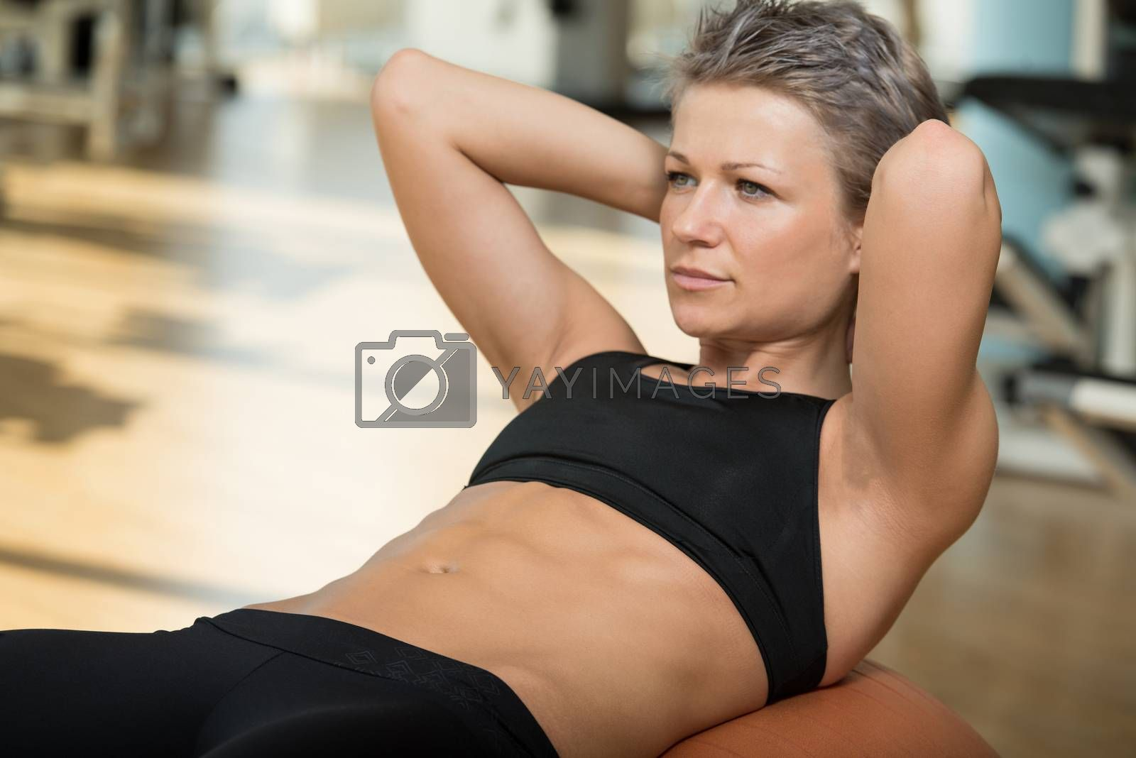 Royalty free image of Attractive Woman Doing Sit-Ups With Exercise Ball by JalePhoto