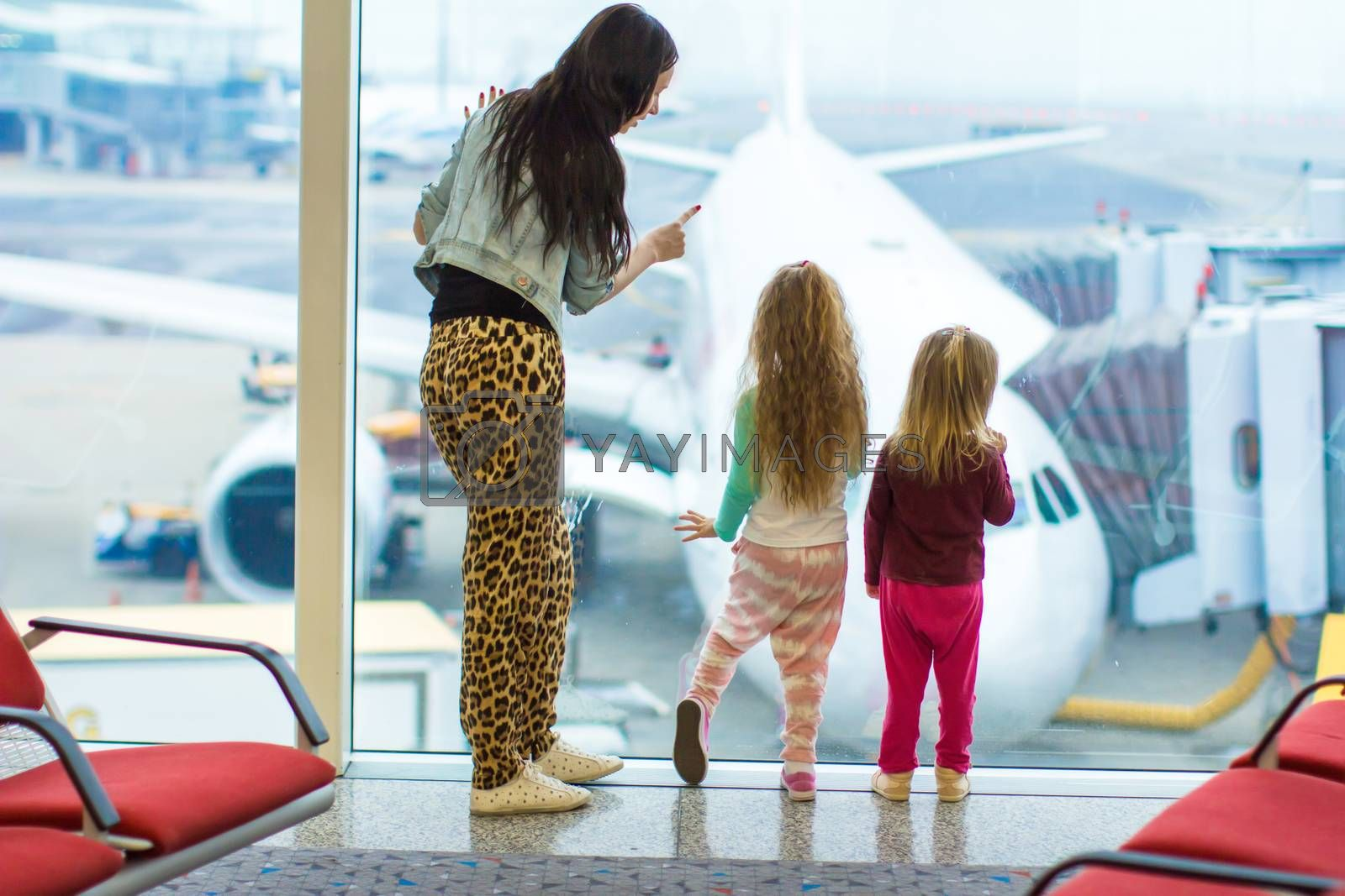 Little girls with their young mother at the large window at the airport