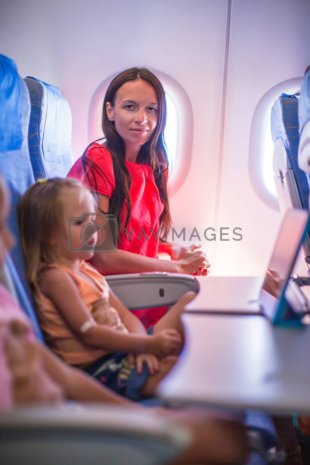 Young mother with her little daughters in the plane