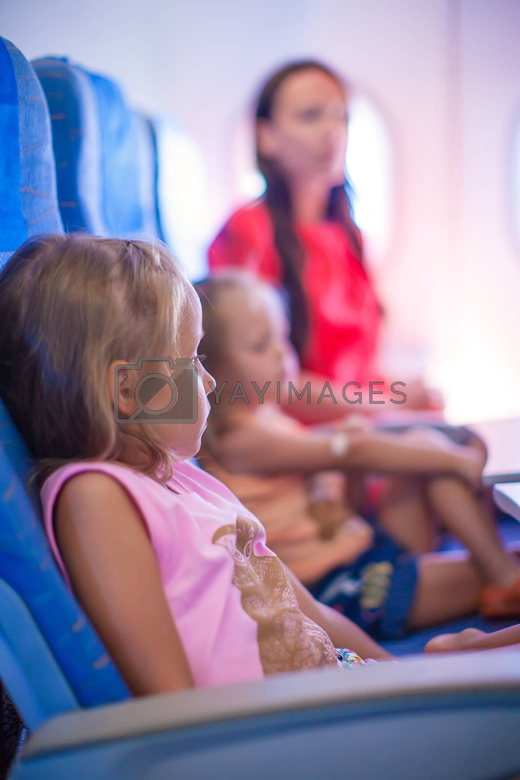 Little girls and young mother in the airplane