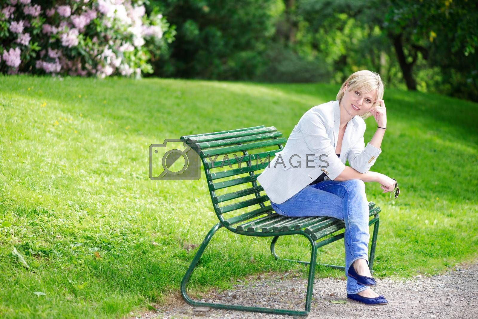 Handsome blond woman on bench looking at camera by Nanisimova