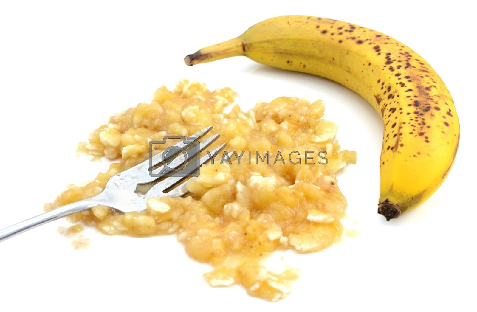 Closeup of mashed banana with fork and an unpeeled fruit by sarahdoow